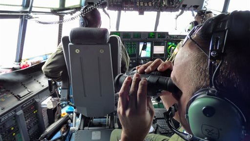 In this image released by the U.S. Coast Guard, Petty Officer 1st Class Mike Crosby, right, scans the surface of the Atlantic Ocean through his binoculars while in the cockpit of a Coast Guard HC-130J, Tuesday, July 28, 2015, while searching for Florida teens Perry Cohen and Austin Stephanos, Tuesday, July 28, 2015. The Coast Guard pressed ahead with a fifth day of searches for the boys while their families coordinated air searches of their own. (Senior Chief Petty Officer Sarah B. Foster/U.S. Coast Guard via AP)