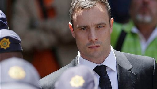 FILE - In this Friday, Oct. 17, 2014 file photo, Oscar Pistorius is escorted by police officers as he leaves the high court in Pretoria, South Africa. Pistorius is  to be released from jail Tuesday, Oct. 20, 2015 under house arrest. (AP Photo/Themba Hadebe, File)