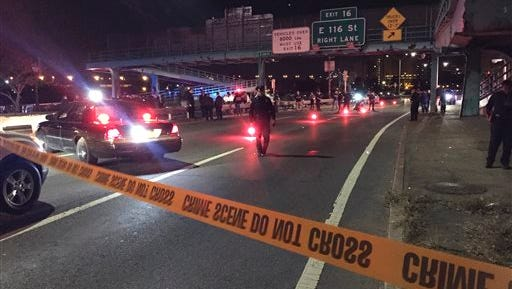 Police officers investigate along FDR Drive at East 120 Street on Tuesday, Oct. 20, 2015, in New York where a New York City police officer was fatally shot. Officer Randolph Holder, 33, died after being shot in the head in a gun battle while pursuing a suspect following a report of shots fired, police said. (AP Photo/Michael Balsamo)