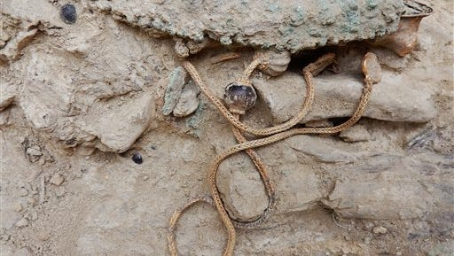This picture provided by Greece's Culture Ministry on Monday, Oct. 26, 2015, shows a long gold chain, decorated with semi-precious stones and hammered-gold plant decorations, as it was found in a 3,500-year-old warrior's tomb. Authorities say a 3,500-year-old, treasure-filled grave of a warrior has been discovered near an ancient palace in southern Greece. The Culture Ministry says the grave is the most spectacular discovery of its kind from the Mycenaean era in more than six decades. It contained about 1,400 artefacts, including gold and silver jewelry, cups, bronze vases, engraved gemstones and an ornate ivory-and gilt-hilted sword. (Greek Culture Ministry via AP)