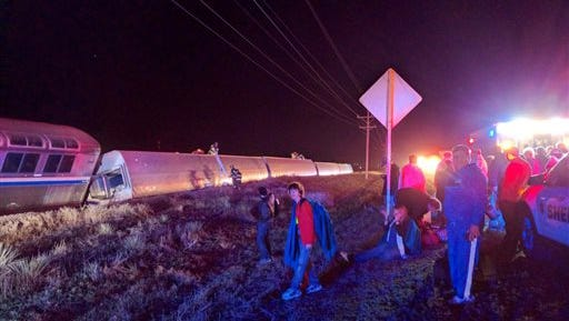 Passengers gather after a train derailed near Dodge City, Kan., Monday, March 14, 2016. An Amtrak statement says the train was traveling from Los Angeles to Chicago early Monday when it derailed just after midnight. (Daniel Szczerba via AP) MANDATORY CREDIT