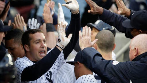 New York Yankees' Mark Teixeira is greeted in the dugout after hitting a three-run home run against the Houston Astros during the seventh inning of a baseball game Thursday, April 7, 2016, in New York.