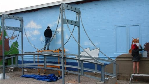 In this April 30, 2016, photo, Traverse City artist Peter Abrami, center, and Interlochen Arts Academy visual arts student Bella Rios of West Hartford, Conn., paint portions of a mural on the side of the Great Lakes Children's Museum building in Traverse City. The museum now has its own smaller version of the Mackinac Bridge connecting Michigan's Upper and Lower peninsulas.