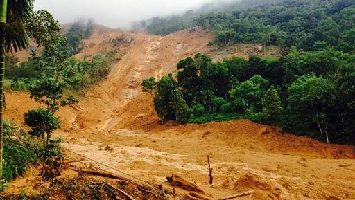 The scene after a massive landslide in  Kegalle District, about 72 kilometers (45 miles) north of Colombo, Sri Lanka, Wednesday, May 18, 2016. Massive landslides triggered by torrential rains crashed down onto three villages in the central hills of Sri Lanka, and more than 200 families were missing Wednesday and feared buried under the mud and debris, the Sri Lankan Red Cross said. (AP Photo/Eranga Jayawardena)