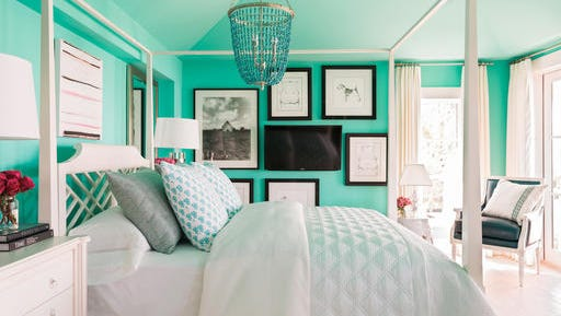 This undated photo provided by HGTV shows a bedroom with a television creatively mounted on the wall that keeps it from standing out too much or detracting from the design of the rest of the room.