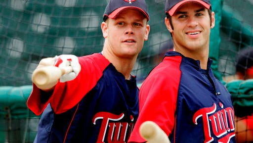 In this March 20, 2008 file photo, Minnesota Twins first baseman Justin Morneau, left, and catcher Joe Mauer joke with players in the Cincinnati Reds dugout prior to a Spring Training baseball game in Fort Myers, Fla.