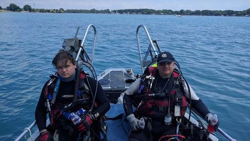 St. Clair County Sheriff Dive Team members Jared Daniel and Mark Peltier prepare to search the St. Clair River for a missing swimmer Tuesday.