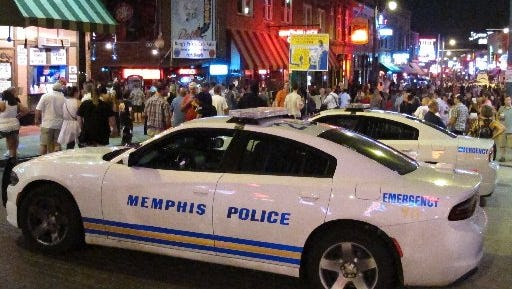 In this Saturday, June 11, 2016 photo, Police cars are parked on Beale Street in Memphis, Tenn. Tourists and locals who plan to partake in the blues bars, dance clubs and barbecue joints on Memphis' Beale Street on Saturday nights will have to bring along some extra cash. In response to a spate of violence near the famous drag, officials have begun charging a $10 entrance fee from those who want to party on Beale Street after 10 p.m. on its busiest night of the week.
