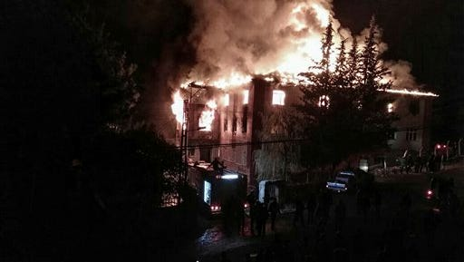 Flames rise from a fire in a school dormitory, in Aladag, Adana in southern Turkey, Tuesday, Nov. 29, 2016. A fire at a middle school dormitory for girls in southern Turkey has left over ten people dead and over a dozen injured, a Turkish governor and state-run media said.