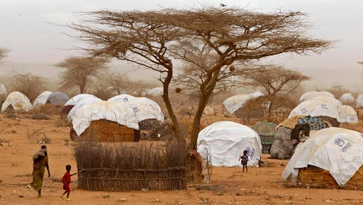 FILE - In this Thursday, Aug. 4, 2011 file photo, refugees walk amongst huts at a refugee camp in Dadaab, Kenya. About 140 Somali refugees whose resettlement in the United States this week was stopped by President Donald Trump's executive order have been sent back to Dadaab refugee camp in northern Kenya, one of the refugees said Saturday, Feb. 4, 2017.