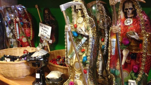 Statues of La Santa Muerte are displayed at the Masks y Mas art store in Albuquerque, N.M.