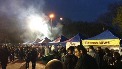 This April 22, 2017 photo shows the Queens Night Market in New York City's Corona, Queens, neighborhood, with people waiting on line at Burmese Bites and other food vendor tents. The market showcases about 50 food vendors, many of them immigrants selling examples of cuisine from their home countries, and is modeled on traditional night markets found in Asia. Similar night markets are popping up in other cities around the U.S.