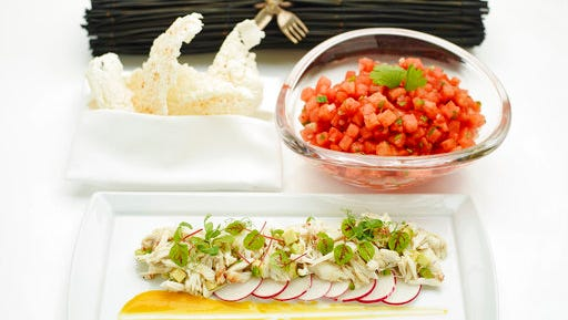 This April 24, 2017 photo provided by The Culinary Institute of America shows an avocado and crab salad garnished with sliced radish and citrus-mango sauce, foreground, a chilled watermelon salad, right, and deep fried rice crisps, left, in Hyde Park, N.Y. This dish is from a recipe by the CIA.