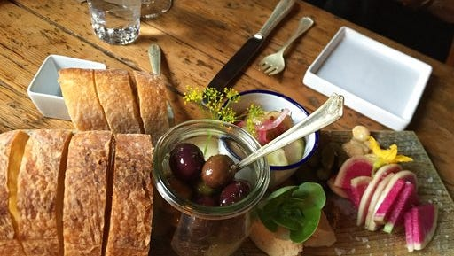 """This Aug. 24, 2016 photo shows bread, olives and other pre-dinner nibbles served at The Lost Kitchen in Freedom, Maine, before the meal begins. The chef and owner Erin French got thousands of phone calls this year on April 1 when she opened reservations for the season for her 40-seat restaurant in an old mill in a tiny Maine town. French has just come out with a cookbook called """"The Lost Kitchen: Recipes and A Good Life Found in Freedom, Maine,"""" telling the remarkable story of her career from a teenager working in her dad's diner to giving dinner parties in her apartment to running a successful restaurant."""