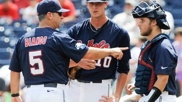 Ole Miss coach Mike Bianco (5) talks to pitcher Chris Ellis (10) and catcher Austin Knight, right, in the fourth inning of an NCAA College World Series baseball game against Virginia in Omaha, Neb., Saturday, June 21, 2014. (AP Photo/Eric Francis)