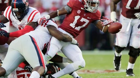 Alabama running back Kenyan Drake (17) fumbles as he is hit by Mississippi defensive tackle Woodrow Hamilton (56) during the first half of an NCAA college football game in Tuscaloosa, Ala., Saturday, Sept. 28, 2013. (AP Photo/Dave Martin)