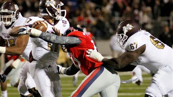 Mississippi State offensive linesman Tobias Smith (67) can't help quarterback Tyler Russell as Mississippi defensive end C.J. Johnson (10) hits him as he throws a fourth-quarter pass in an NCAA college football game in Oxford, Miss., Saturday, Nov. 24, 2012. Mississippi won 41-24. (AP Photo/Rogelio V. Solis)