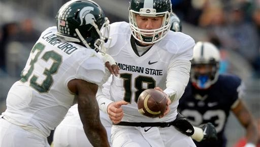 Michigan State quarterback Connor Cook hands the ball to Jeremy Langford during the first half of an NCAA college football game against Penn Statae in State College, Pa., Saturday, Nov. 29, 2014. (AP Photo/York Daily Record, Chris Dunn)