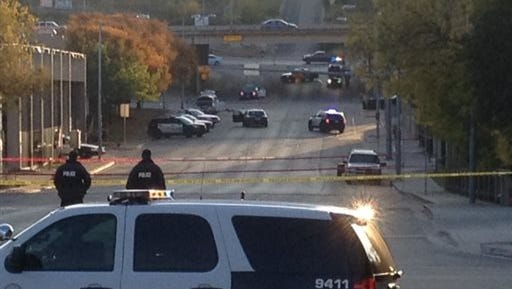 Police tape marks off the scene after authorities shot back at a man who they say opened fire on the Mexican Consulate, police headquarters and other downtown buildings early Friday in Austin, Texas. In the distance, police cars surround the suspect's vehicle parked near the Interstate 35 overpass.