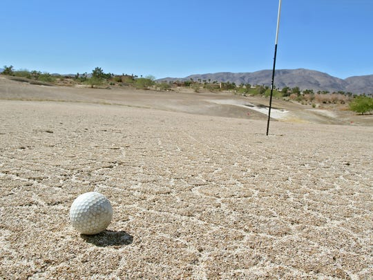 A golf ball sits on a green that hasn't been watered for years at Rams Hill Country Club in Borrego Springs.