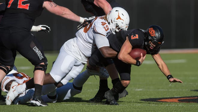 Texas defensive lineman Ta'Quon Graham tackles Oklahoma State quarterback Spencer Sanders during the second quarter of Saturday's Longhorns win at Boone Pickens Stadium. Sanders committed three of OSU's four turnovers.