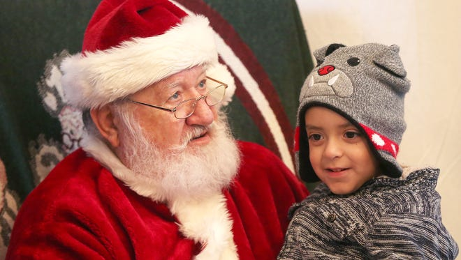 Marco Aurelio, 4, visits Santa Claus during the Christmas at Old Fort Concho event in 2016.