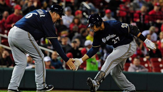 Milwaukee Brewers center fielder Carlos Gomez, right, celebrates with third base coach Ed Sedar after hitting a solo home run during the seventh inning at Busch Stadium.