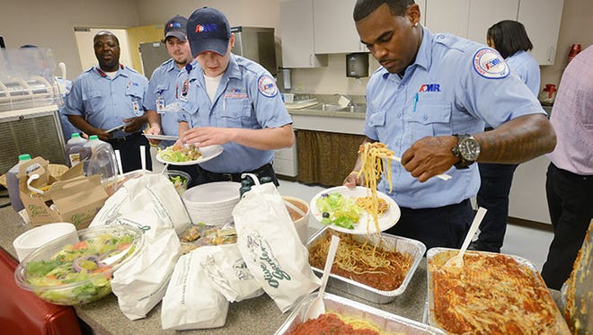 American Medical Response staff, from left, B.J. Wells, Bradley Roberts, Josh McPherson and Otis Smith help themselves to pasta, soup, salad and breadsticks from Olive Garden while at AMR's Jackson headquarters on Monday.