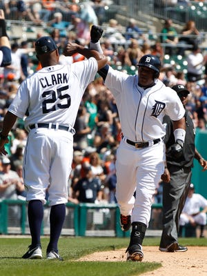 Detroit Tigers third base coach Dave Clark congratulates Yoenis Cespedes as he rounds third base after his home run to tie the game 1-1 in the fourth inning against the Chicago White Sox on April 17, 2015, at Comerica Park in Detroit.