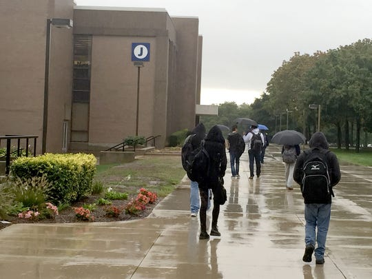 Macomb Community College students at the Warren campus using umbrellas and hoods to cover themselves from rain as they walk Sept. 29, 2016. Christina Hall/Detroit Free Press