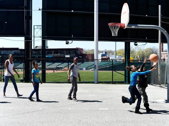 "From left, Ahik Schoch, 3, Aquarius Scott, Semaj Smith, 10, Kanisha Kirkland, Jessazhia Mays, 12, and Anya Nixon, 8, play basketball on a court behind PeoplesBank Park in York recently. The construction of the stadium 10 years ago had a profound effect on this city neighborhood, commonly known as ""The Swamp."" Whether the effects have been good depends on whom you ask."