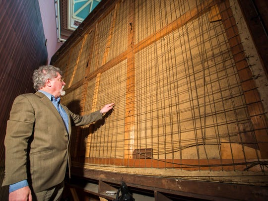 "Bob Joly, director of the St. Johnsbury Athenaeum, examines the back of Albert Bierstadt's ""The Domes of the Yosemite"" on Friday, January 13, 2017. The painting has been pulled away from the wall in preparation for transport to Miami where it will be restored."