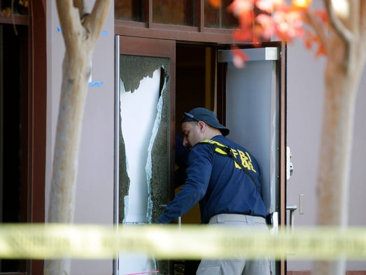 A investigator works the site of the mass shooting