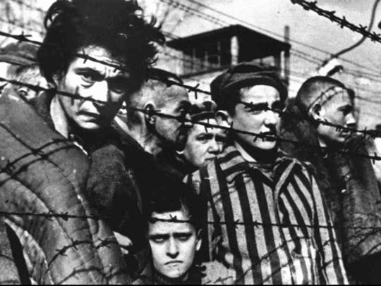 Auschwitz Inmates appear behind barbed wire during