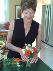 Colleen Kilpatrick arranges flowers for her house,