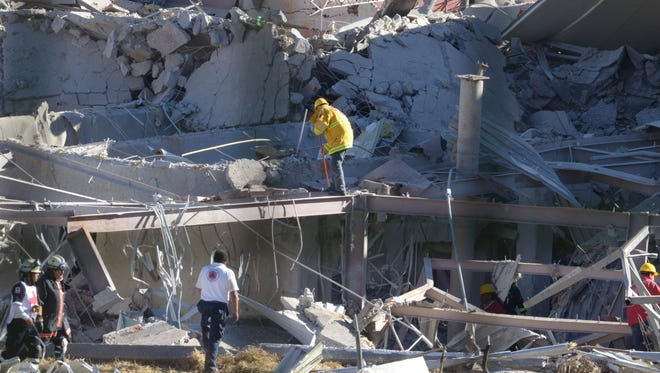 Rescuers work amid the wreckage caused by an explosion in a hospital in Cuajimalpa, Mexico City, on Jan. 29, 2015.