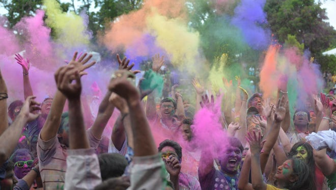 The crowd throws colored powder skyward at the first Festival of Colors in Novi last year.