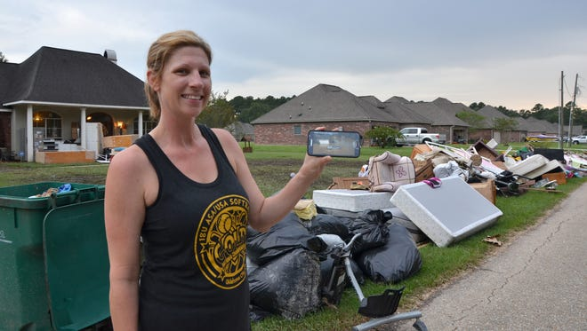 Denham Springs resident Lori Johnston stands in front of her house and still manages to smile while showing an image of her flood-soaked property.  While her house held several feet of water, she and her family were busy rescuing, cooking and housing friends.  She was extremely grateful despite the devastation.