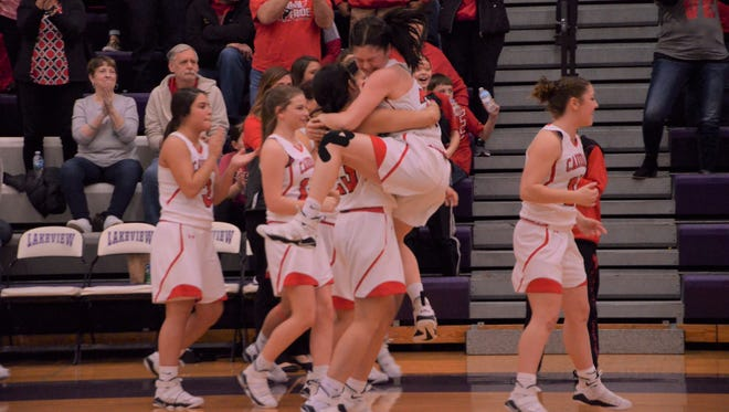 Coldwater players celebrate after defeating Harper Creek to claim a Class A district championship at Lakeview High School on March 2, 2018.