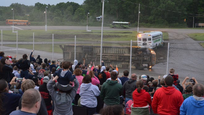 The sold out crowd celebrates a bus tipping over during the figure-eight bus race at Galesburg Speedway on Sunday, June 3, 2018.