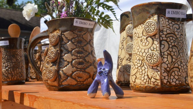 A purple cat stands watch along a shelve of Charlie Imboden's pottery at the Lexington Fine Arts Fair on Aug. 5, 2018, in Lexington, Michigan.