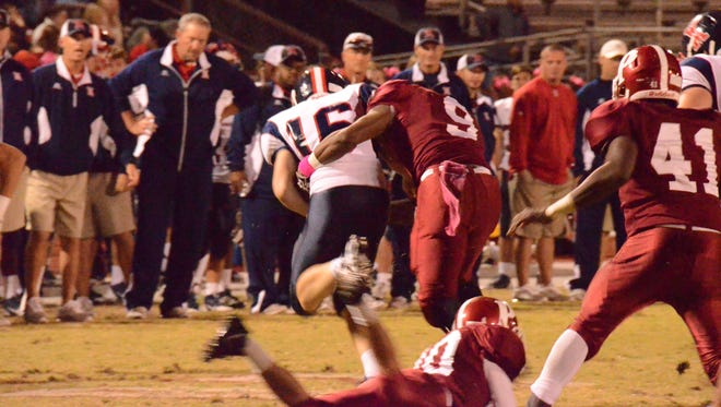 Pineville senior Shaquille Harbor (9) tackles West Monroe quarterback Wes Tatum (16) during Pineville's home loss last week. Harbor began the season at running back but moved to defense two weeks ago.