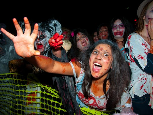 Alexa Cervantes reaches for the camera  during the  6th annual Zombie Walk on Main Street.