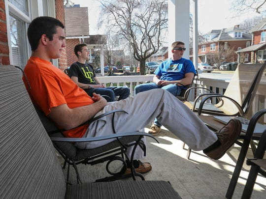 University of Delaware seniors (left) Joe Moye, Mark Murphy and Ryan Corey sit on the porch of their rented house on Prospect Avenue in Newark Wednesday. Rooftop parties, like the one involving a fatal fall on March 19, are common in Newark.