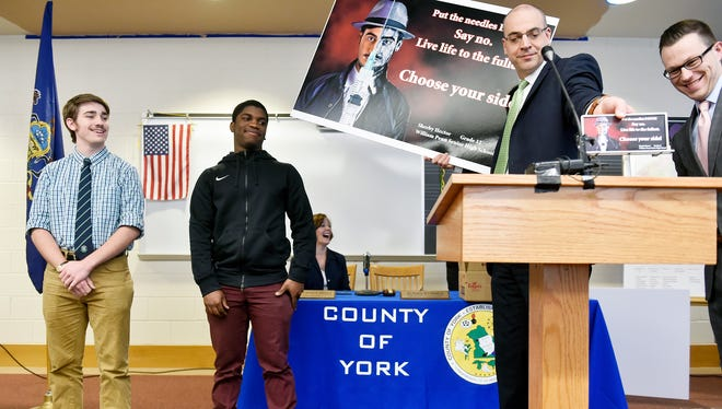 York County Chief Deputy Prosecutor David Sunday, second from right, displays a winning billboard art entry by William Penn senior Sherby Hector, second from left, after a York County Board of Commissioners meeting Wednesday, in William Penn's library. The York County Heroin Task Force partnered with York County schools, Lamar Advertising and Penn Waste to sponsor a Heroin Awareness Billboard Contest, for which almost 20 students submitted art to warn against heroin use.