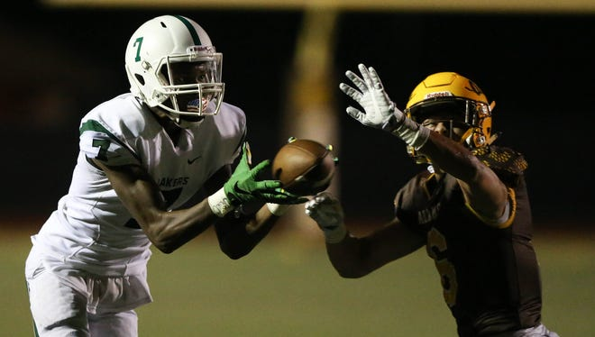 West Bloomfield's Tre Mosley makes a catch against Rochester Adams' Chase Kareta and takes it 99 yards for the winning touchdown in the fourth quarter Friday, Sept. 22, 2017 in Rochester.