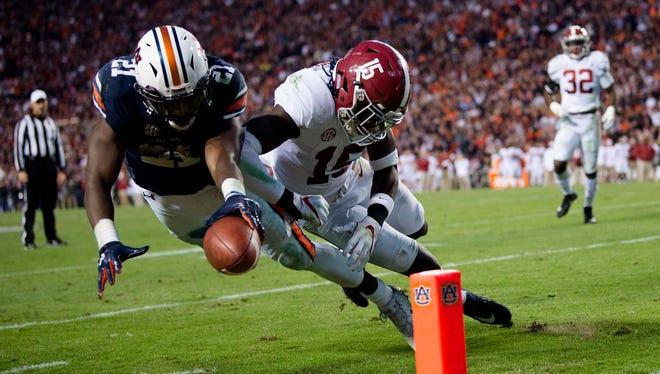 Auburn running back Kerryon Johnson (21) dives for the end zone and gets a first down as Alabama defensive back Ronnie Harrison (15) knocks him out of bounds during the Iron Bowl NCAA football game between Auburn and Alabama on Saturday, Nov. 25, 2017, in Auburn, Ala.