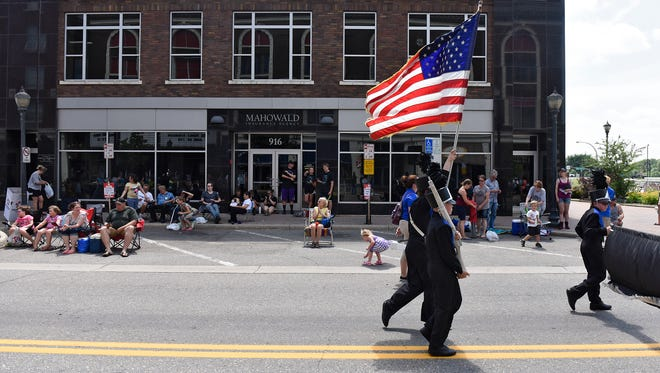 The American Flag brings follows the Owatonna High School marching band near the end of the 2016 Granite City Days Parade in St. Cloud.