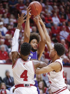 Barret Benson (25) of the Northwestern Wildcats tries to break the Indiana Hoosiers press of Indiana Hoosiers guard Robert Johnson (4) and Indiana Hoosiers forward Clifton Moore (22) at Simon Skjodt Assembly Hall in Bloomington, Ind., on Wednesday, Jan. 9, 2018.