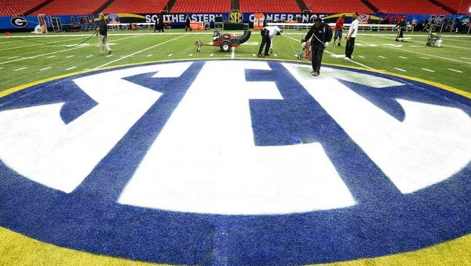 The SEC emblem is touched-up at midfield at Georgia Dome in Atlanta, Ga. before the SEC Championship Game on Saturday December 7, 2013.